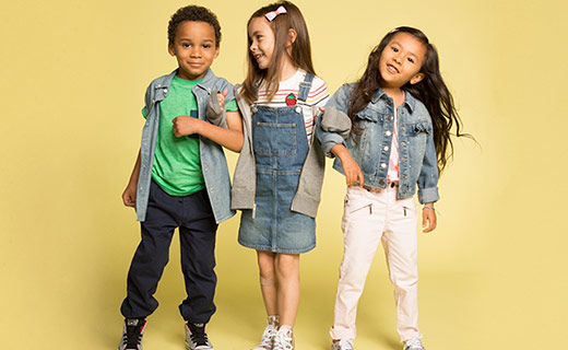 Three children dressed for school with a yellow background