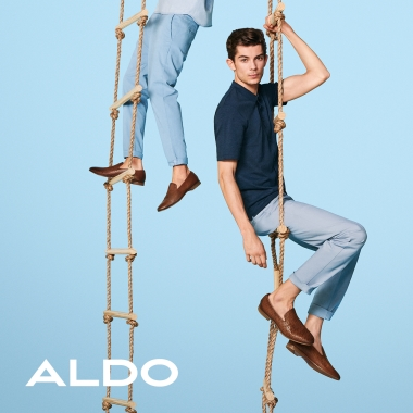 Aldo logo. Cropped image showing person from the waist down on rope ladder and man on another rope ladder sitting.