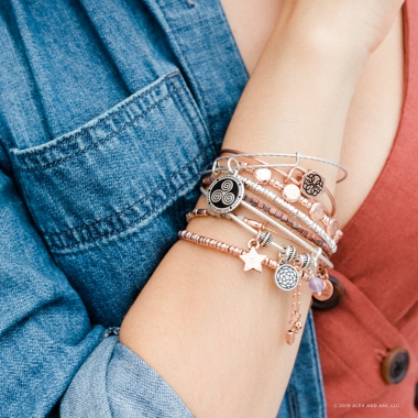 Cropped photo of woman's arm with variety different bracelets stacked,