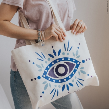 Cropped image of woman from shoulders wearing various bracelets down holding canvas tote bag with Evil Eye design.