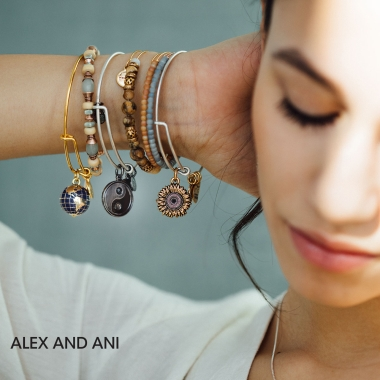 Woman face and arm, wearing multiple bracelets with variety of beads and charms. Alex and Ani logo.