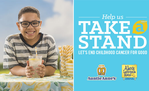 Boy sitting at table smiling holding glass of lemonade. Copy: Help us take a stand. Let's end childhood cancer for good. Auntie Anne's logo. Alex's Lemonade Stand logo.