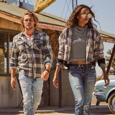 A man wearing ripped jeans with a plaid shirt, a woman wearing ripped jeans, a striped shirt, and a plaid jacket.