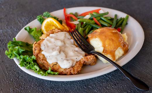 Buttermilk Fried Chicken Breast on lettuce leave with gravy, green beans, mashed potatoes with gravy and lemon slice.