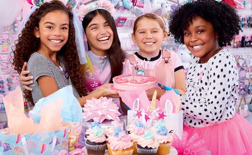4 girls smiling with cupcakes and gift bag.