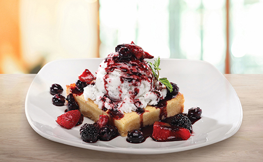 Ooey Gooey Butter Cake with vanilla ice cream and fresh berries shown on white plate
