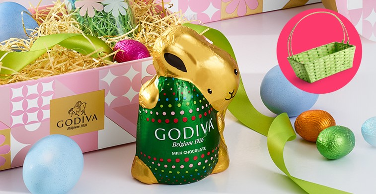 Godiva Milk Chocolate bunny shape foil wrapped chocolate, foil wrapped eggs, colored egg, green wicker basket, Godiva pink and white decorative box filled with colorful straw, ribbon and 1 colored egg with 1 foil covered egg.