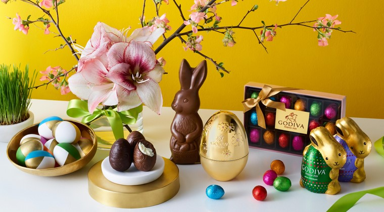 Green plant, floral arrangement with pink flowers, bowl of colored eggs, 3 chocolate eggs, unwrapped chocolate shaped bunny, gold Godiva egg, multi-color small foil wrapped eggs, ribbon tied box of multi-colored small foil wrapped eggs and two foil wrapped chocolate bunnies.