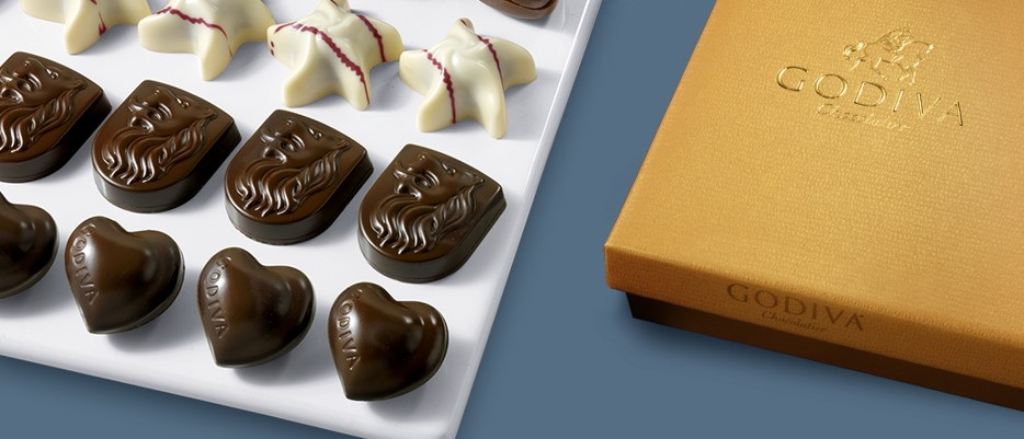 Gold Godiva box next to a row of chocolate hearts, white chocolate stars and chocolate lion on plate
