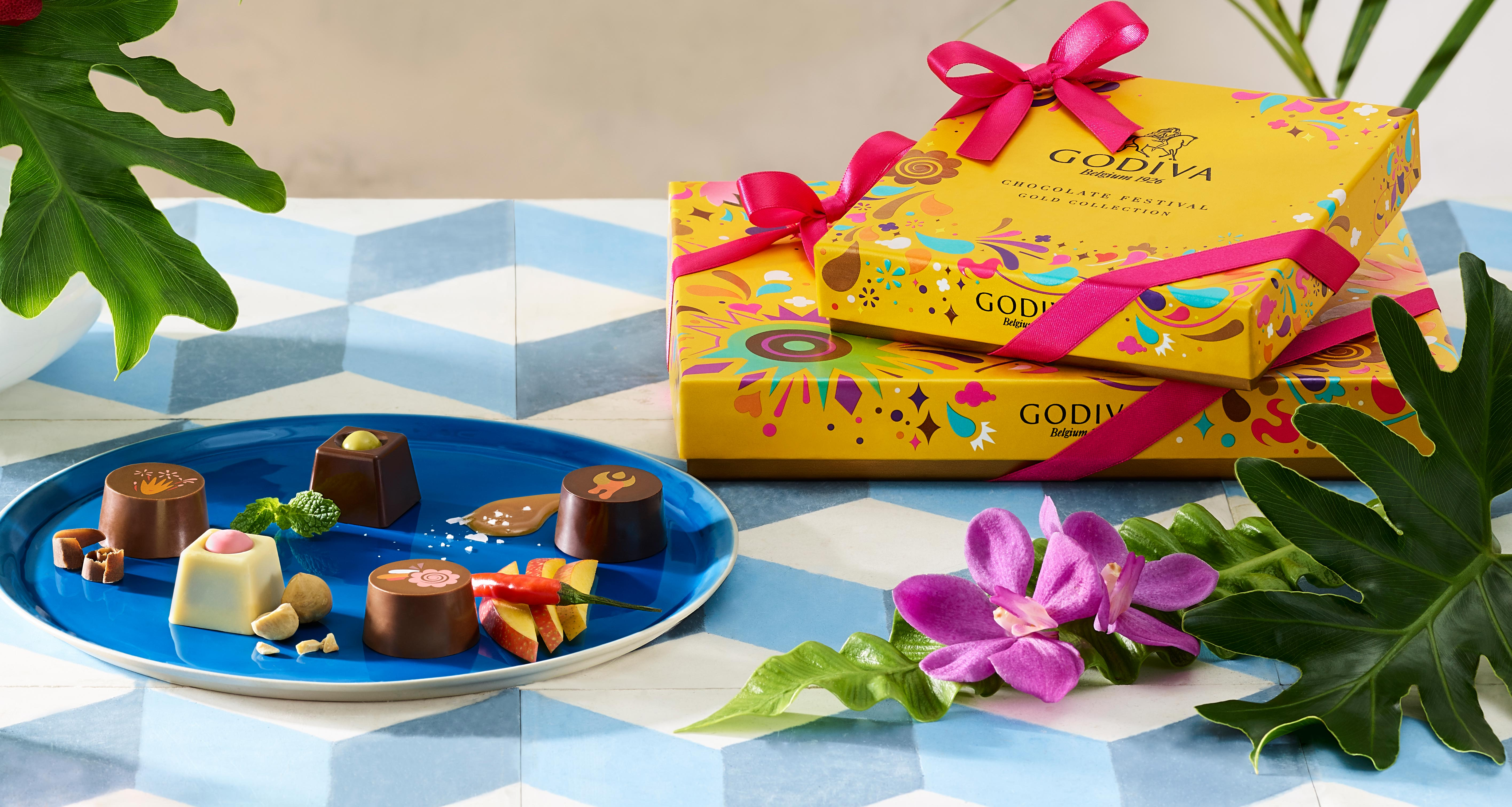 Tropical flower and plants, two Godiva chocolate boxes, miscellaneous chocolates on blue plate.