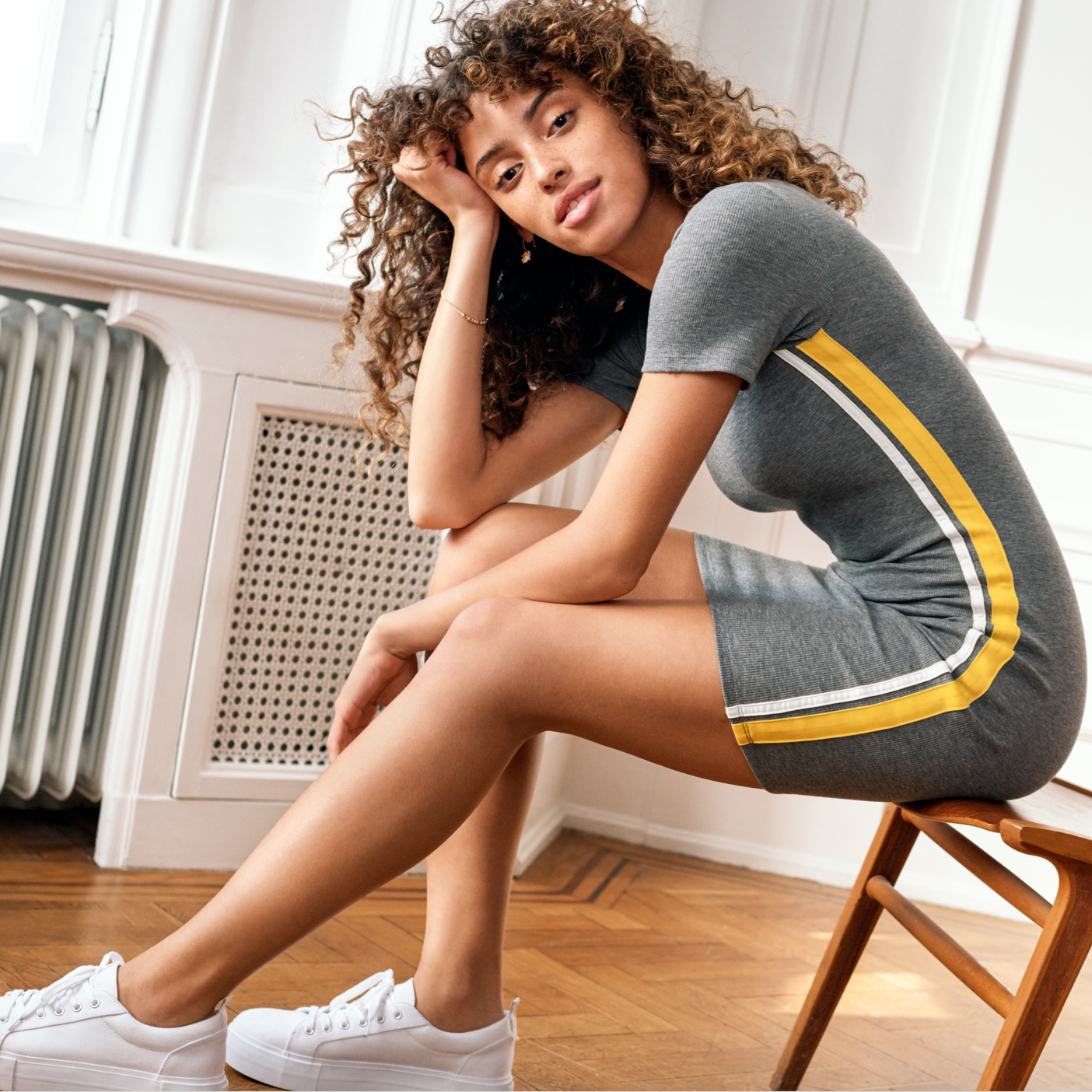 Woman sitting on edge of chair leaning on her elbow wearing gray knit dress with yellow and white stripe down the side, wearing white tennis shoes.