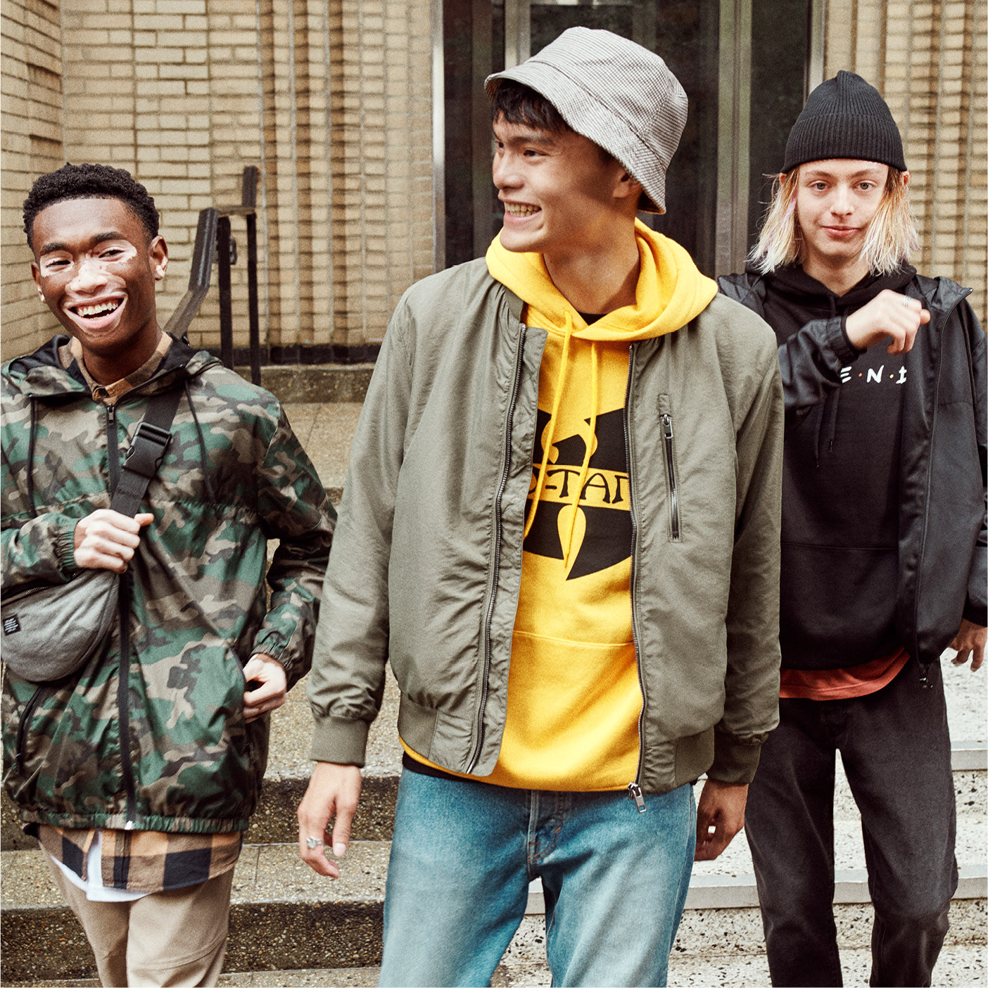 Three teen boys, wearing jackets, two with hats walking together one with fanny pack around his shoulder walking down stairs.