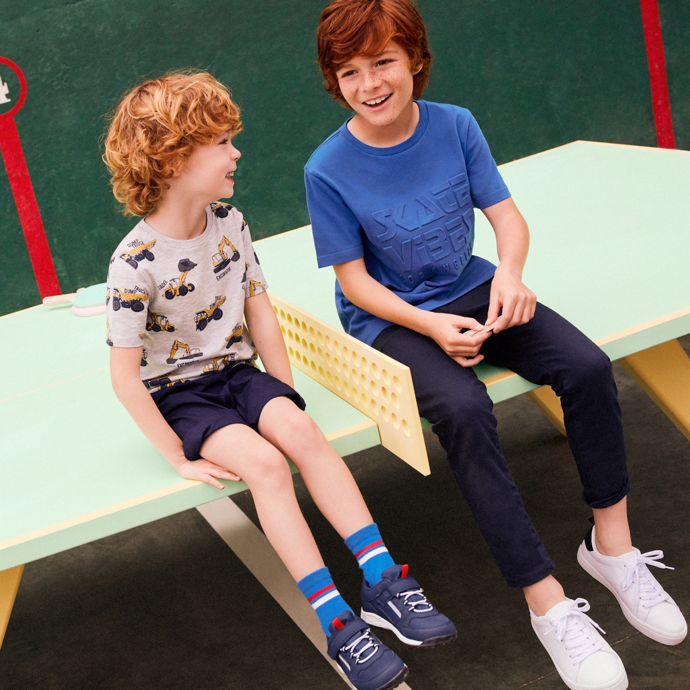 Two smiling boys sitting on table, one wearing navy jeans and blue t-shirt, the other wearing navy shorts and heavy machine print t-shirt.