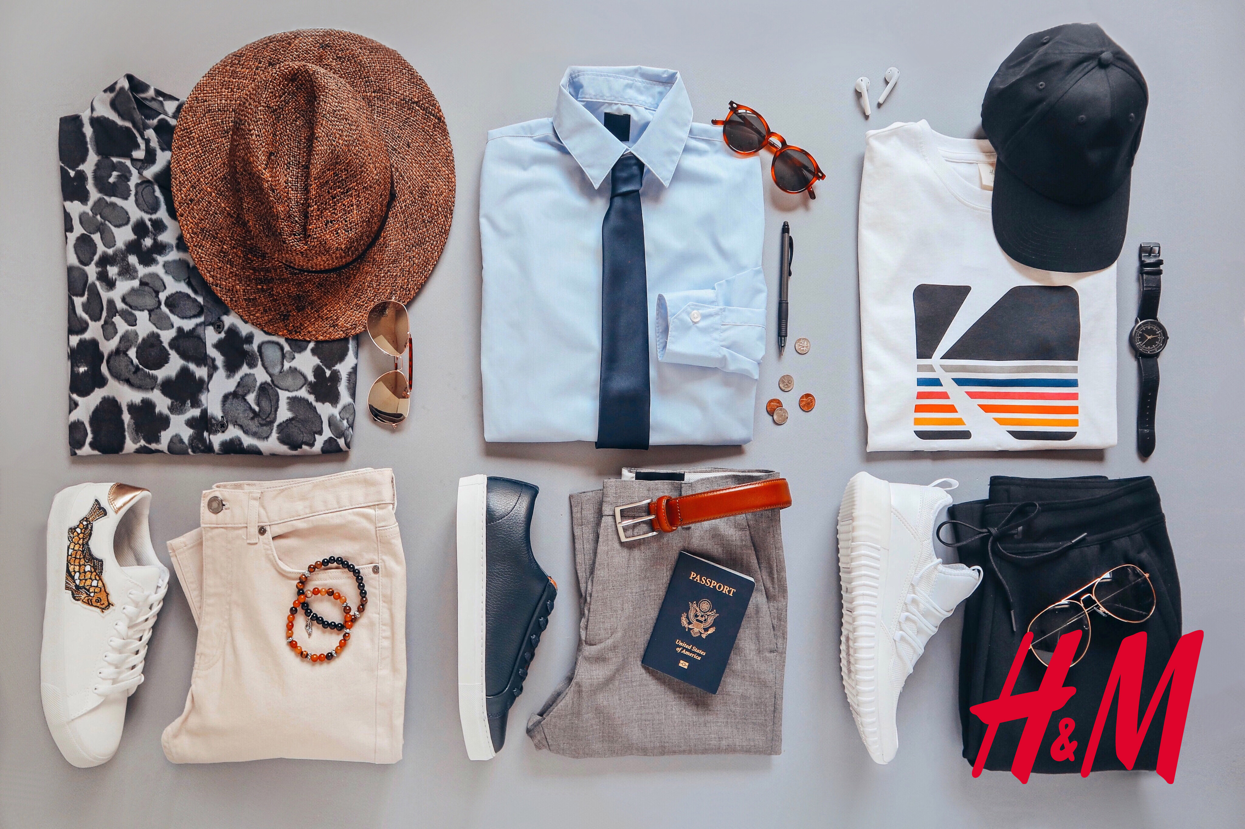 Shown, selection of men's clothing sorted by stylish, sporty and business looks.  Includes, shirts, shoes, pants, sunglasses, belt, watch, airpods, pen, loose change, and passport.
