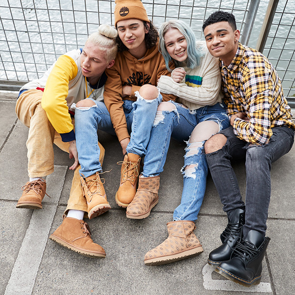 Four teen/young adults sitting in a small group on the ground showing in such a way that you can see their shoes.  All wearing a variety of shoes/boots.