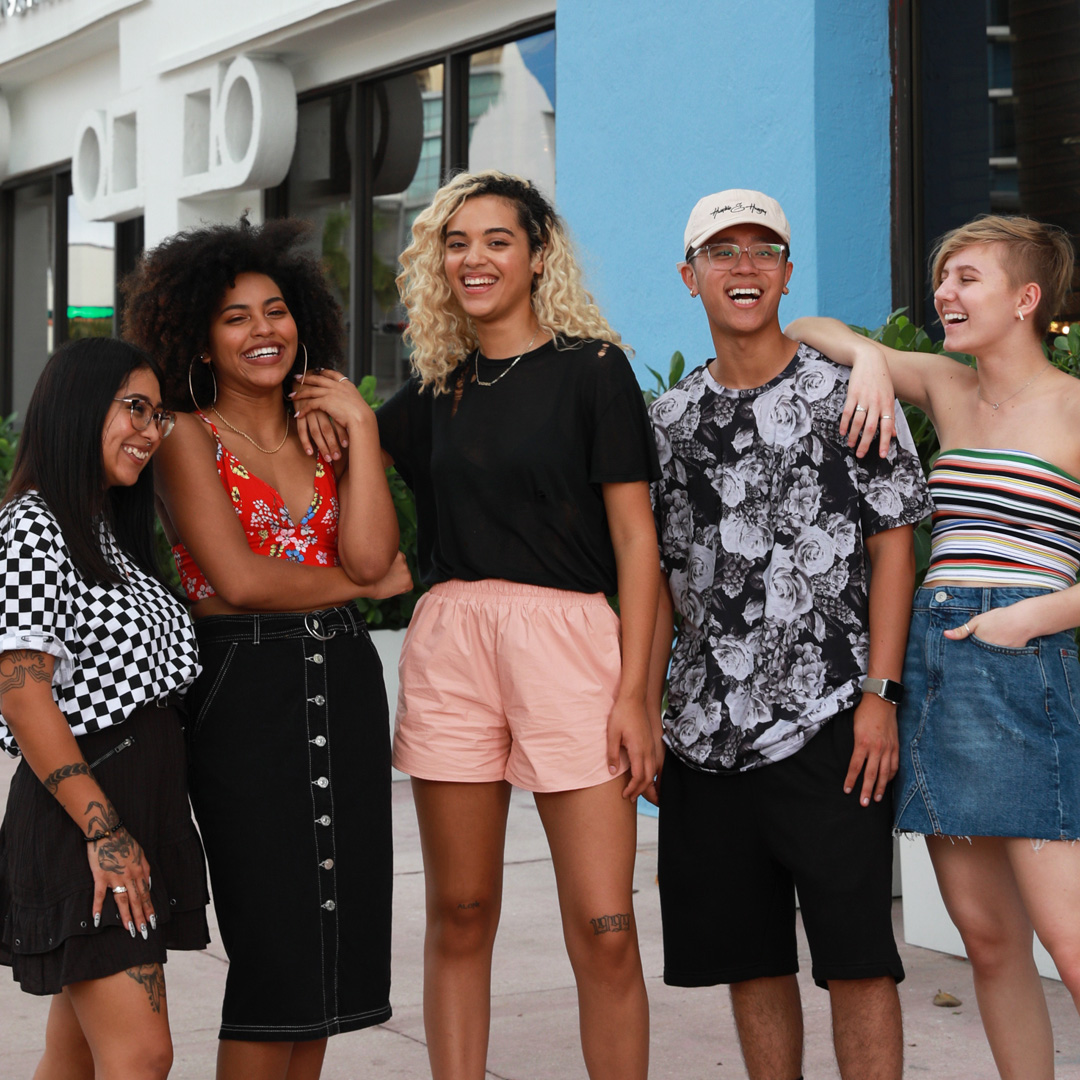 Group of teens/young adults standing together laughing all wearing summer attire, shorts, tank tops, tube tops, skirts.