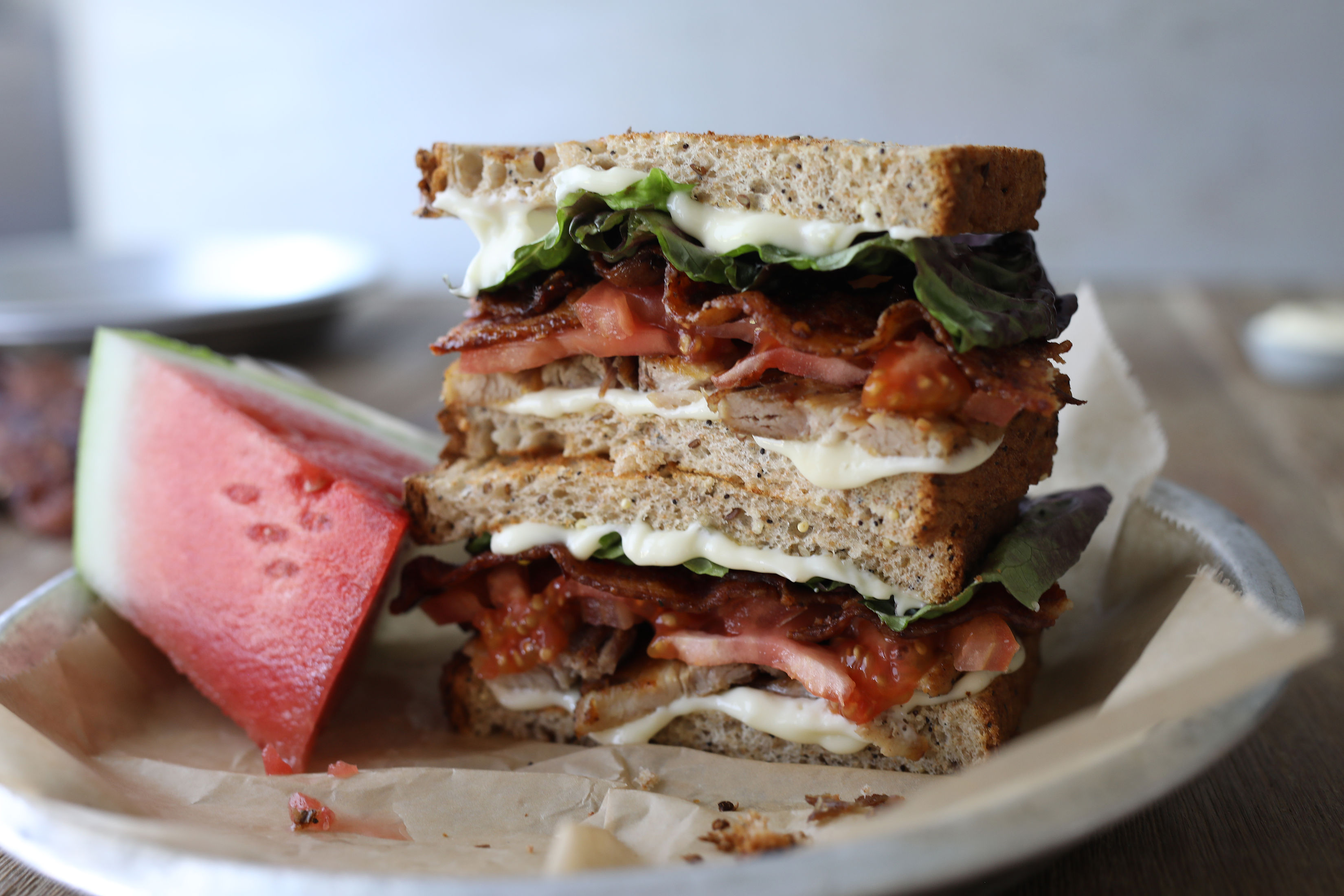 Pork Belly Bacon Lettuce Tomato Sandwich on toast with watermelon slice