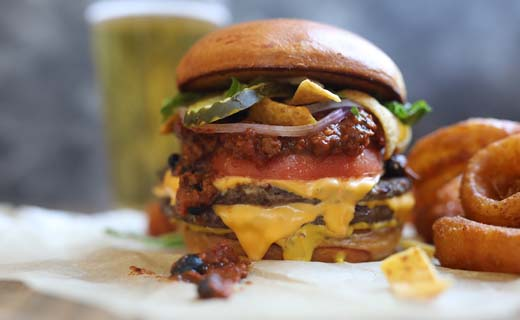 Fritos-Chili Cheeseburger shown (two grilled quarter-pound beef patties, american cheese, housemade chili, liquid blanket ipa mustard, crunchy fritos, shredded lettuce, tomato, onion, pickles)