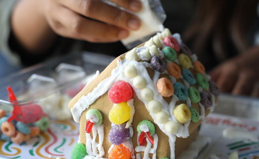 Partially decorated gingerbread house shown with gumdrops and multi-colored fruit cereal being decorated with icing.