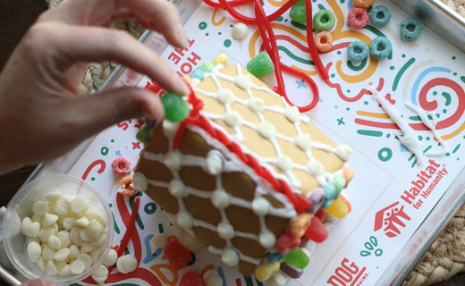 Someone is placing a green gumdrop on a gingerbread house with other candies for decorating shown sitting on a tray with a Habitat for Humanity paper beneath it.