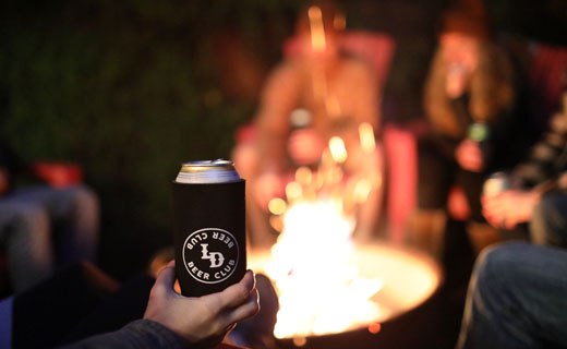 Hand holding beer can with LD Beer Club label shown, and in the background out of focus are people sitting around a fire pit.