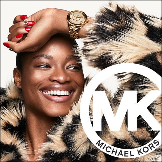 Michael Kors logo. Woman wearing tan and black fur like coat, wearing gold MK watch,