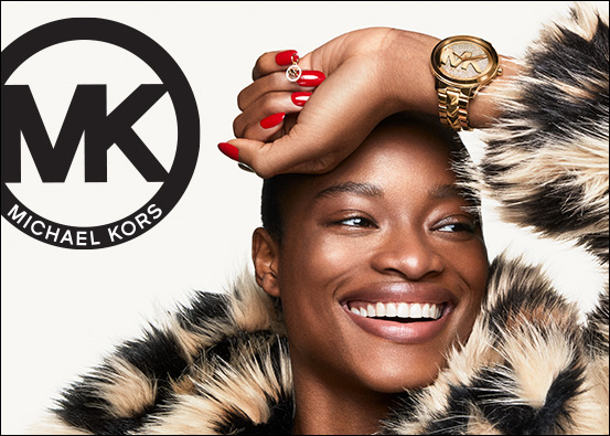 Michael Kors logo. Image: Woman wearing fur coat, she is smiling, her hand is resting on her head showing her red fingernails, gold nail charm and her gold Michael Kors logo watch.