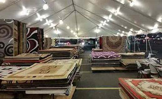 Interior of tent shown with rugs of all shapes, styles and colors shown