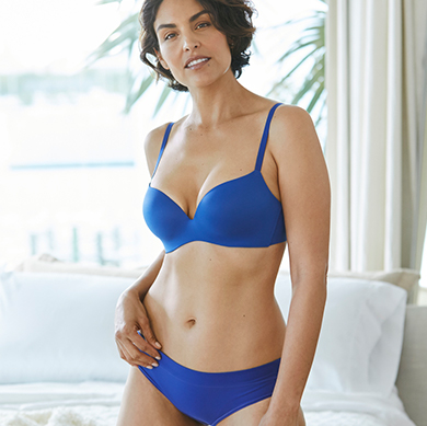Woman wearing Enbliss lifting demi bra and matching underwear in blue