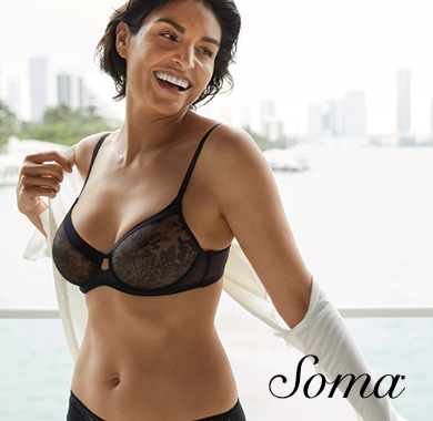 Soma logo. Image: Woman with short black hair removing long sleeve white shirt showing black lace bra and matching panties smiling with a view of the city skyline in the background.