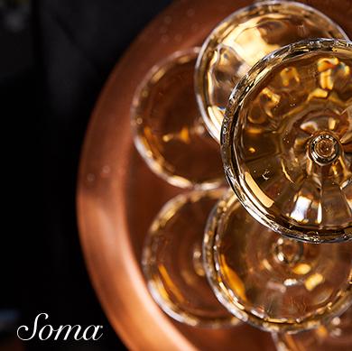 Soma logo. Image: stacked gold tone glassware