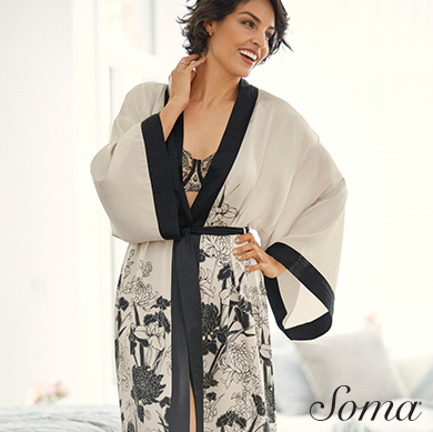 Soma logo. Woman smiling with one hand on hip, one on neck - wearing white and black floral print robe with peak of lace bra showing.