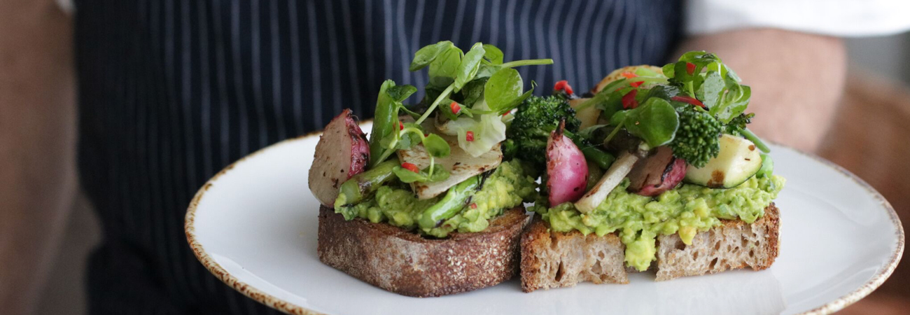 Avocado toast topped with a variety of vegetables