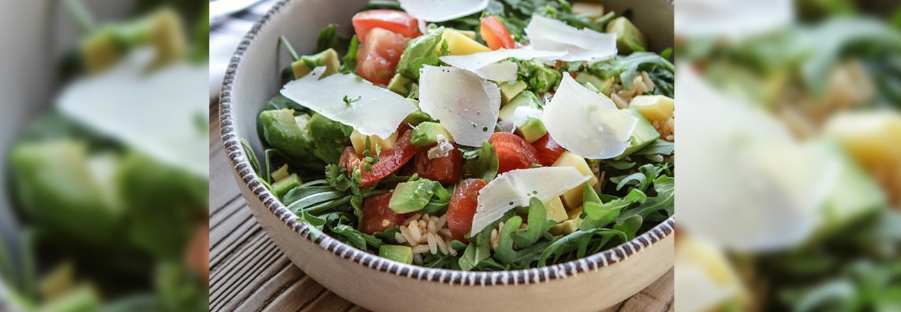 A fresh summer salad with greens, tomato, rice, and shaved cheese