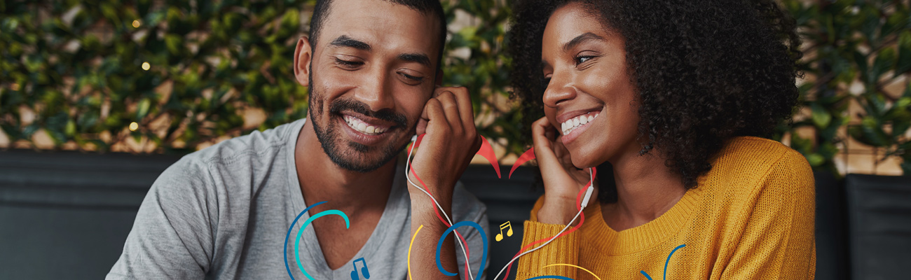 Happy young couple listening to headphones together, with cartoon graphics applied