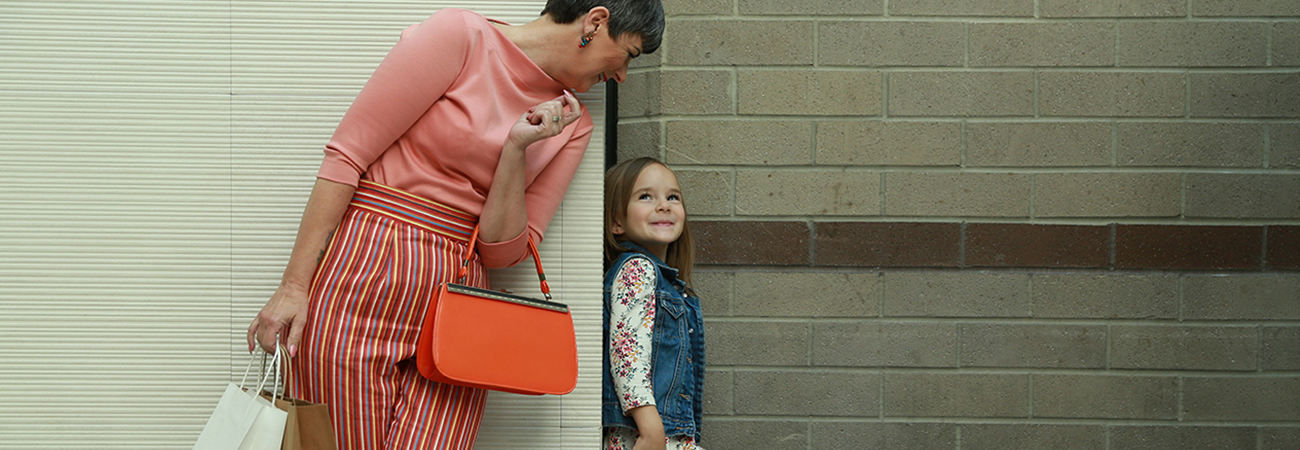 Ultra stylish grandmother and cute granddaughter looking around a corner at each other