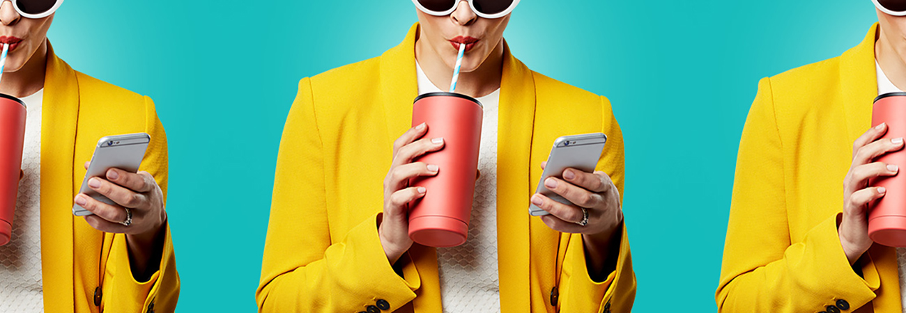 Repeating image of a woman in sunglasses and a yellow blazer drinking a beverage and looking at her phone