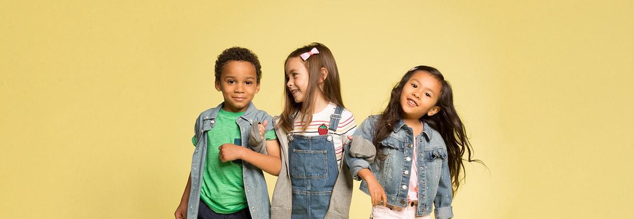3 elementary school kids standing arm-in-arm