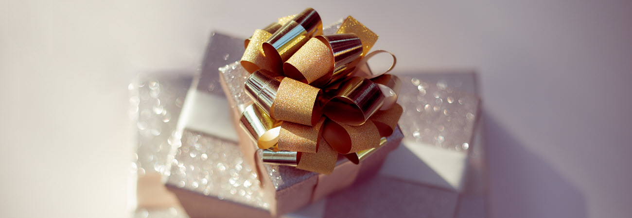 A glittery stack of present in metallic wrapping paper with a gold bow on top