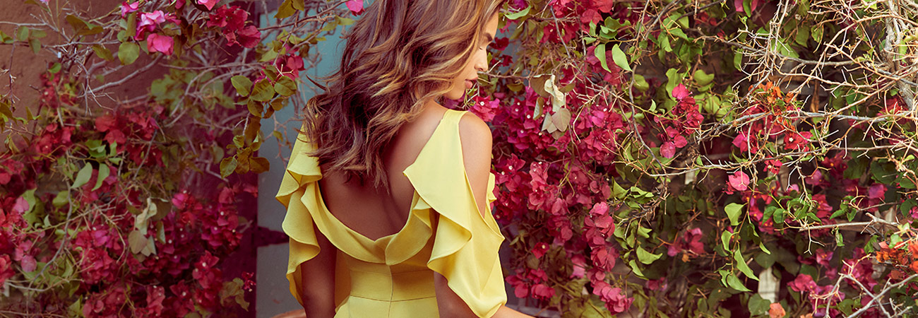 Female model in yellow cold-shoulder dress looking over her shoulder, in front of a wall of bougainvillea
