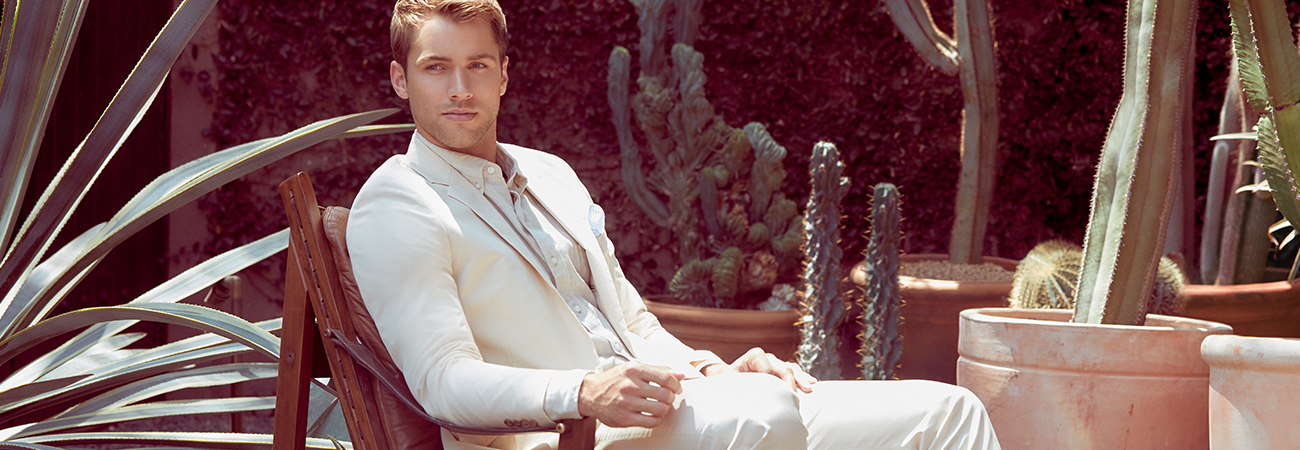 Male model in cream colored sport coat, button-up shirt, and pants sitting in a chair surrounded by cacti
