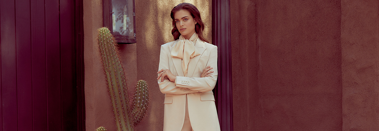 Female model wearing a menswear-inspired cream blazer and scarf standing next to a cactus in front of a stucco wall