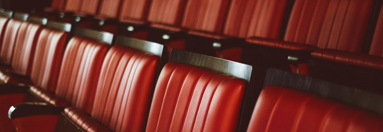 Rows of red movie theater chairs.