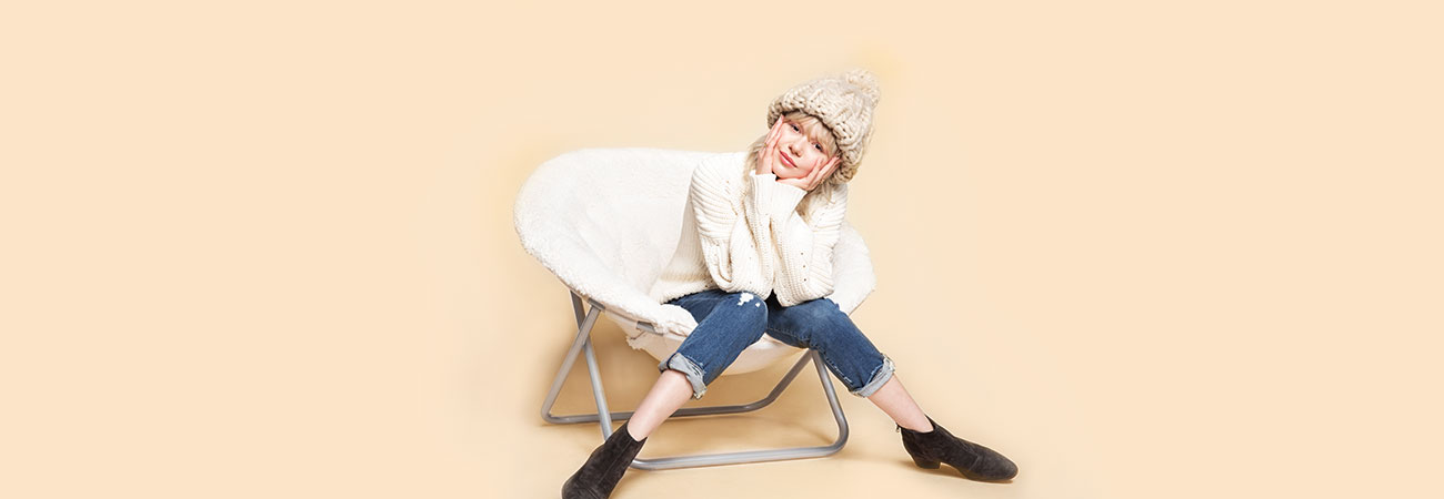 College-aged girl wearing a chunky off-white beanie and sweater, and rolled up jeans, sitting in a round chair