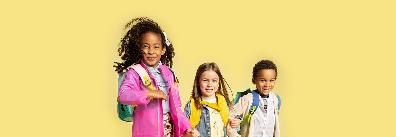 3 elementary school-aged children locked arms, smiling, and wearing fun school clothes against a yellow background