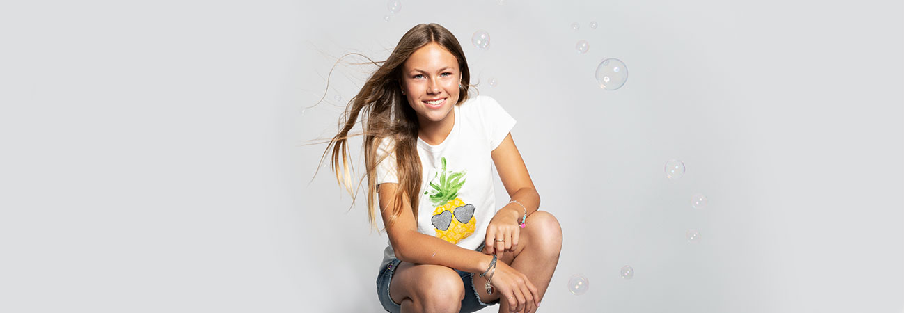 Teen girl in summer clothes crouching down and surrounded by bubbles