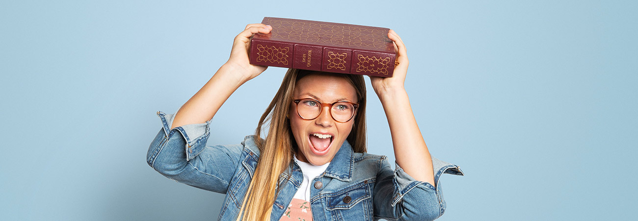 A teenage girl carrying a book over her head