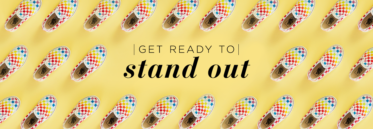 "Rainbow checkboard Vans shoes arranged diagonally on a yellow background. Text reads: ""Get Ready to stand out"""