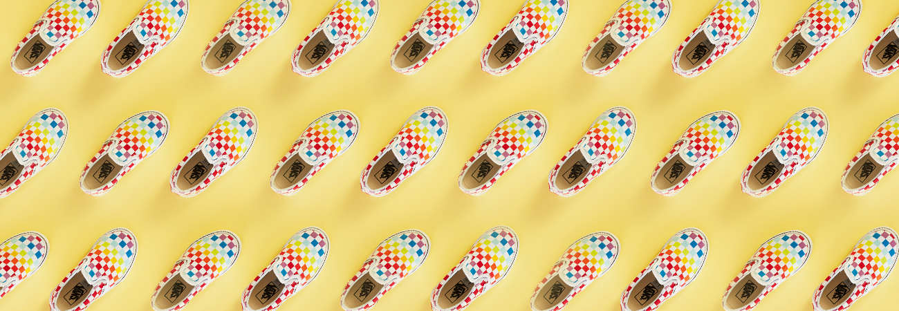 Rainbow checkboard Vans shoes arranged diagonally on a yellow background