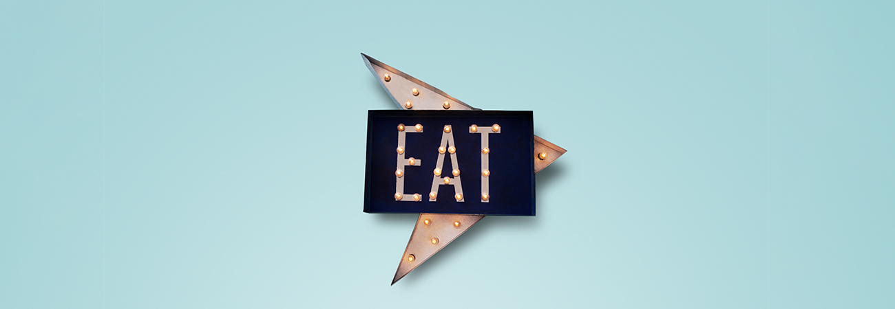 "A light up metal ""Eat"" arrow sign on a blue background"